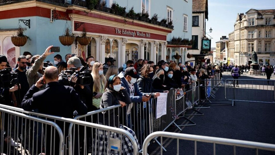 Des gens, pour la plupart masquée, se tiennent derrière une clôture, le long d'une rue.