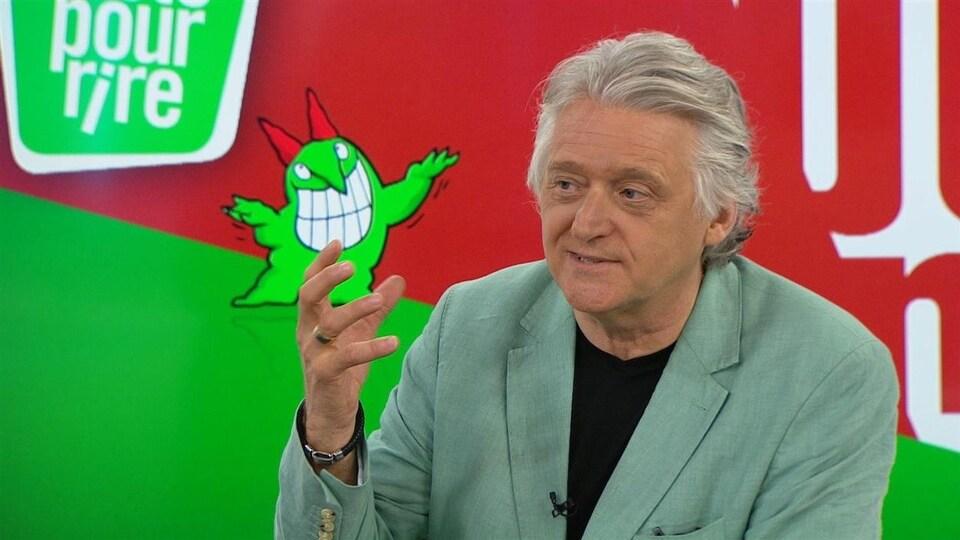 Gilbert Rozon devant l'affiche de Juste pour rire.