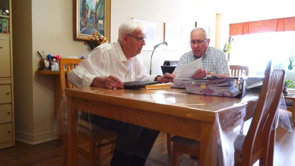 MM. Duchesneau et Pettigrew assis à une table.