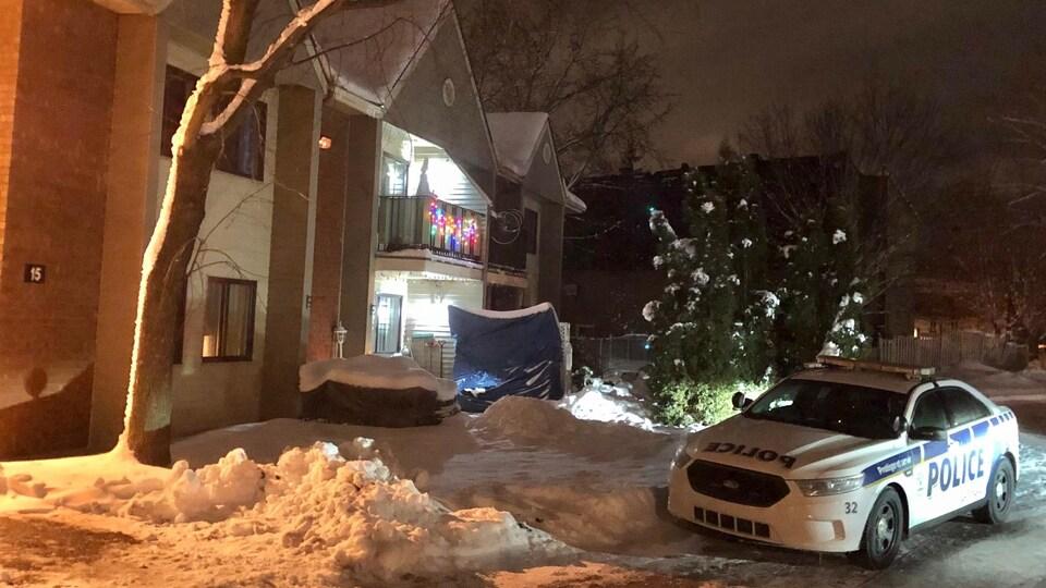 Une voiture de police près d'un édifice de logements à Gatineau la nuit.