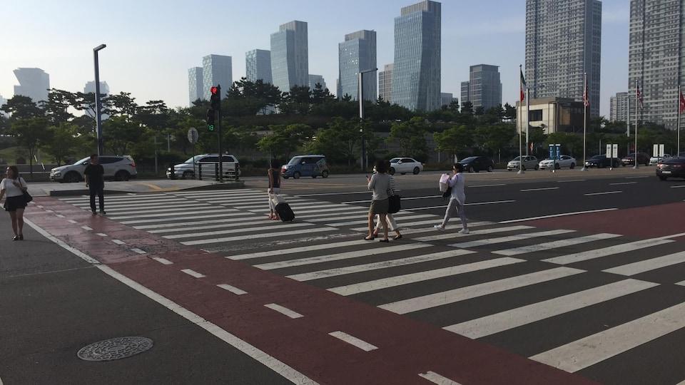 On voit quelques personnes traverser un grand boulevard de Songdo sur un passage pour piétons.