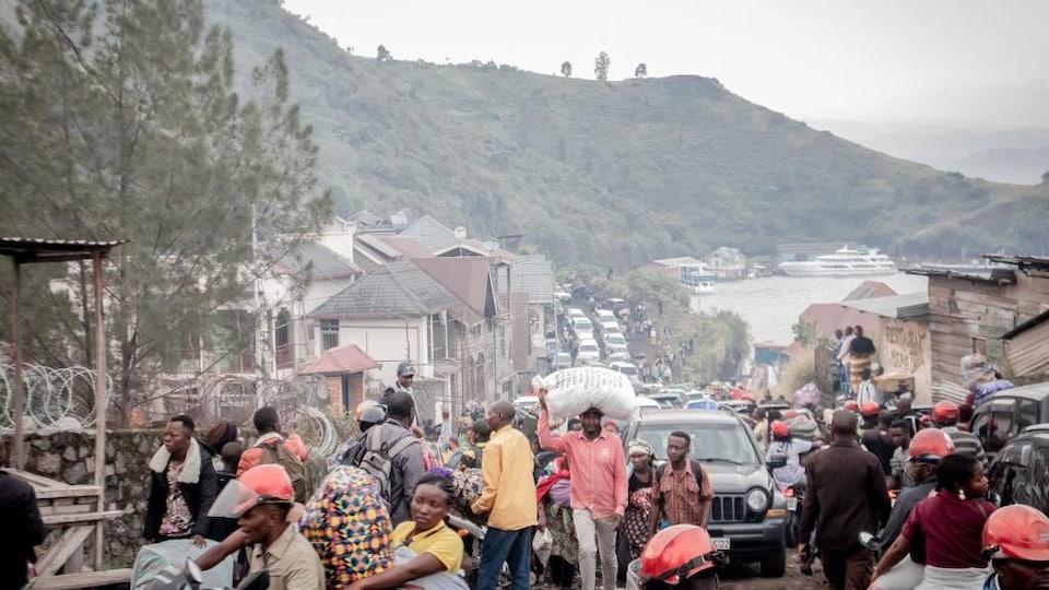 Des dizaines de personnes marchent dans une rue bondée de véhicules.