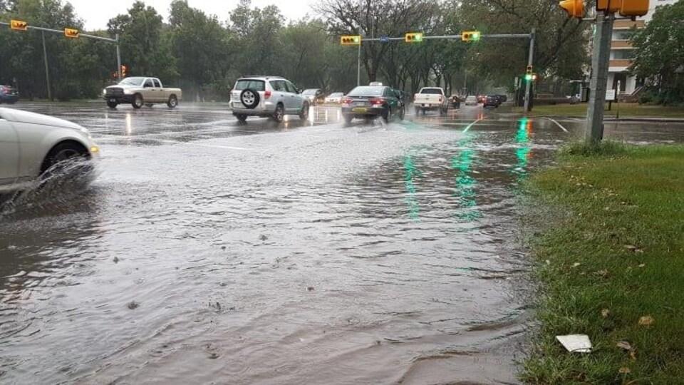 Des voitures traversent une intersection inondée à Regina.