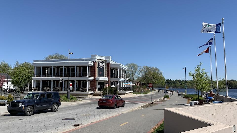 Des voitures et un cycliste se déplacent sur la chaussée.