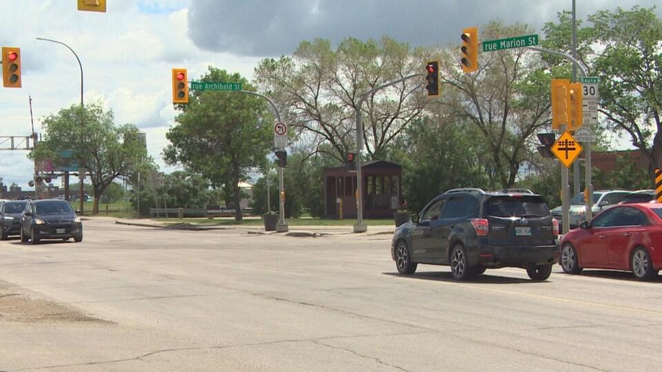 Des voitures, dans les deux sens, arrêtées à des feux de circulation à une intersection. Journée d'été, arbres verts et ciel partiellement couvert.