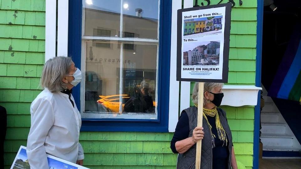 Deux femmes manifestent dans la vile d'Halifax. Une pancarte dénonce le développement de condos sur la rue Queen.