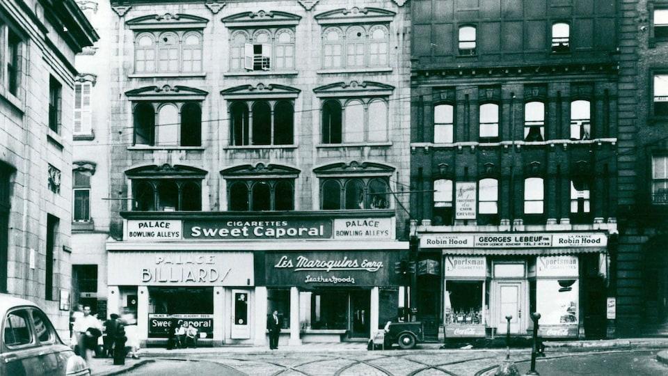 Une vieille photo de l'édifice Monaghan sur la rue Saint-Jean, en noir et blanc, avec des piétons et des voitures