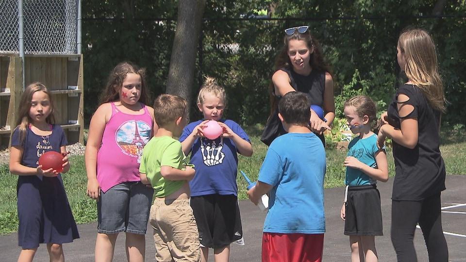 Deux femmes donnent des instructions à des jeunes, qui tiennent des ballons remplis d'eau en les écoutant.