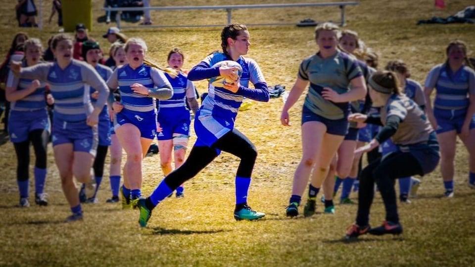 Une jeune joueuse de rugby qui s'élance sur le terrain.