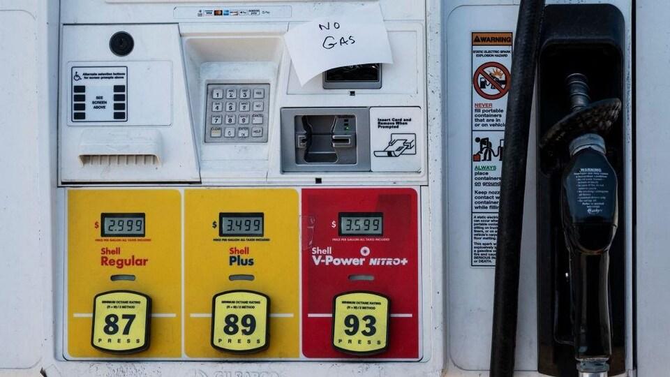 Sur la pompe d'une station-service, un papier indique qu'il n'y a plus d'essence.