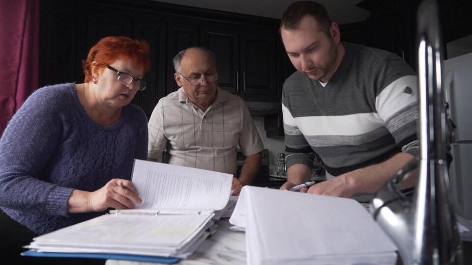 Galina Ilyayeva, Sergey Ilyayev et leur fils Denis regardent des documents.