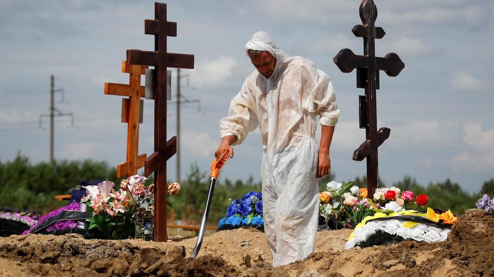 Un homme en combinaison creuse une tombe dans un cimetière.