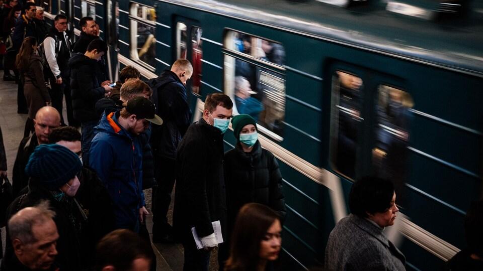 Des usagers du métro, certains portant des masques, attendent sur un quai.
