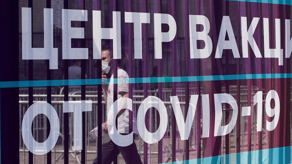 Un homme marche derrière une bannière dans un centre de vaccination contre la COVID-19 au stade Luzhniki à Moscou.