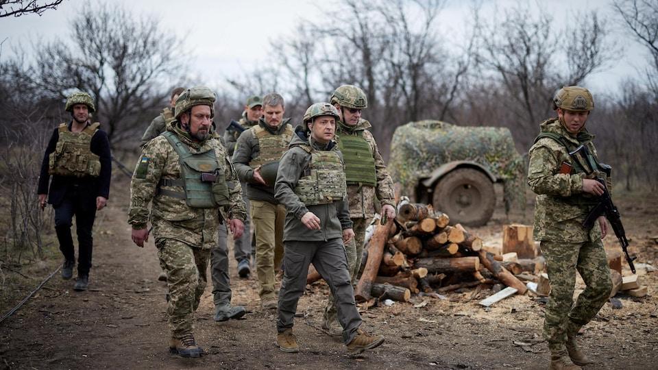 Le président Zelensky, entouré de militaires, porte des vêtements de protection.
