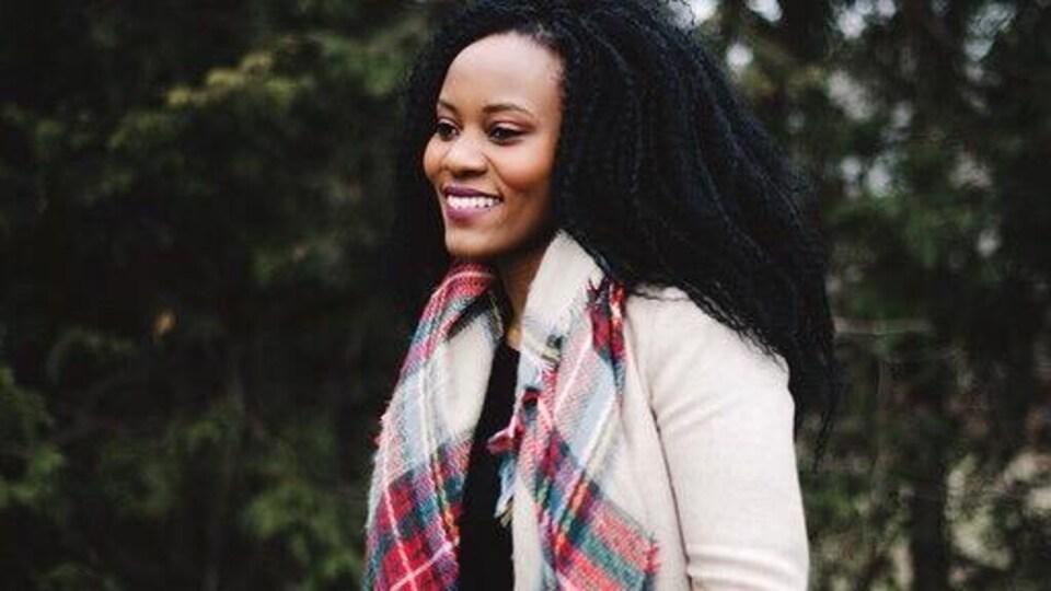 Ruth Maniriho Bansoba, souriante, avec un foulard et un veston rose pâle, à l'extérieur, le jour.