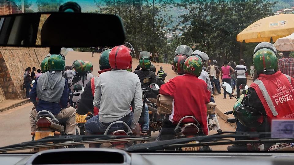 Plusieurs motos-taxis transportent des clients.