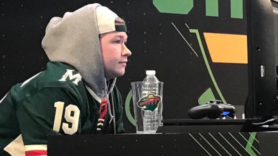 Un jeune garçon assis lors d'une compétition de jeu vidéo au Minnesota.