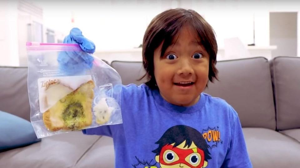 Un jeune garçon étonné tient dans sa main droite un pain moisi dans un sac Ziploc.