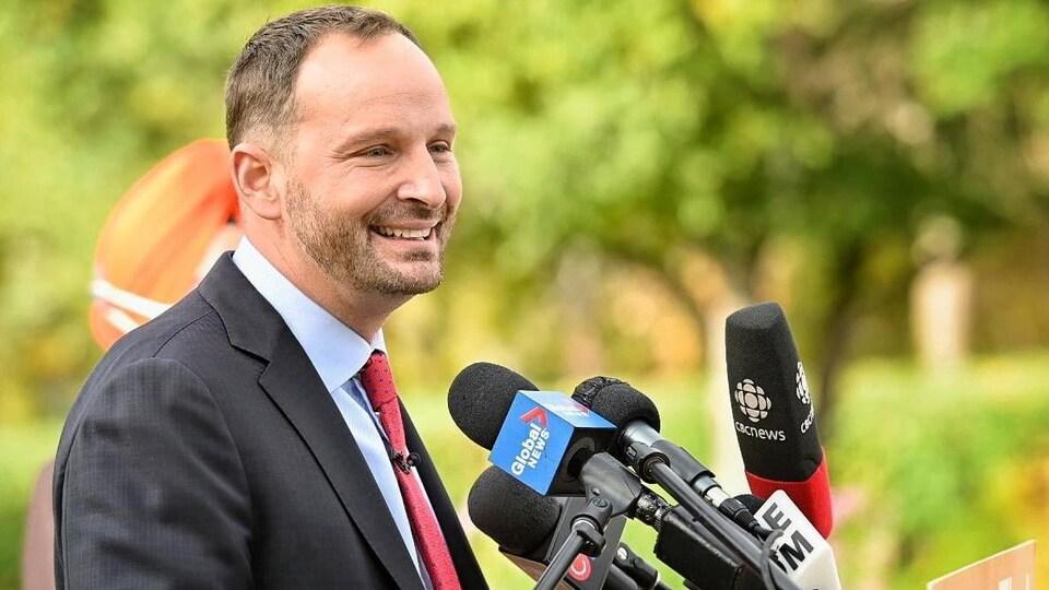 Ryan Meili, tout sourire devant les micros des journalistes.