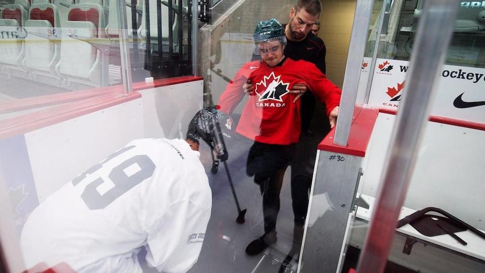 Ryan Straschnitzki reçoit de l'aide pour monter sur la glace.