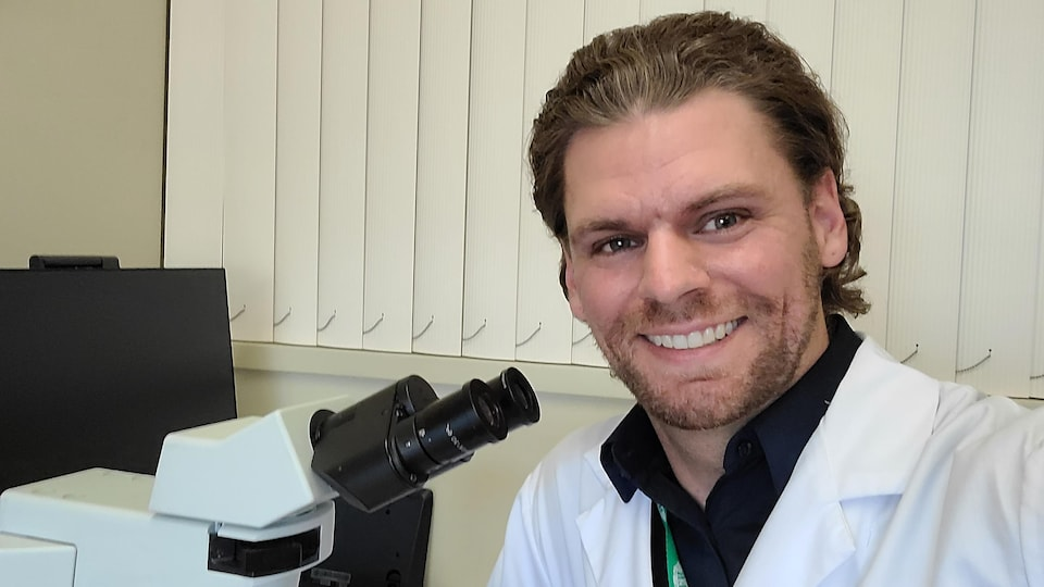 Ryan Wybenga pose dans son bureau devant un microscope.