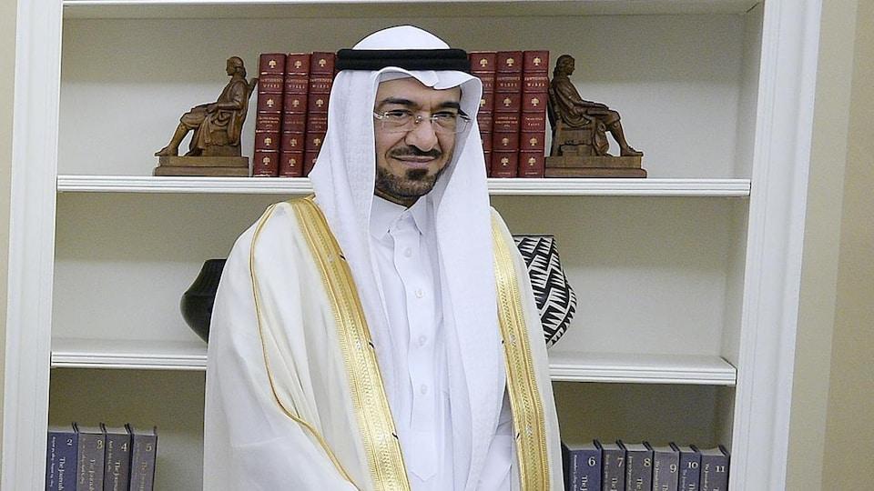 Un homme portant l'habit traditionnel saoudien et des lunettes en face d'une bibliothèque.