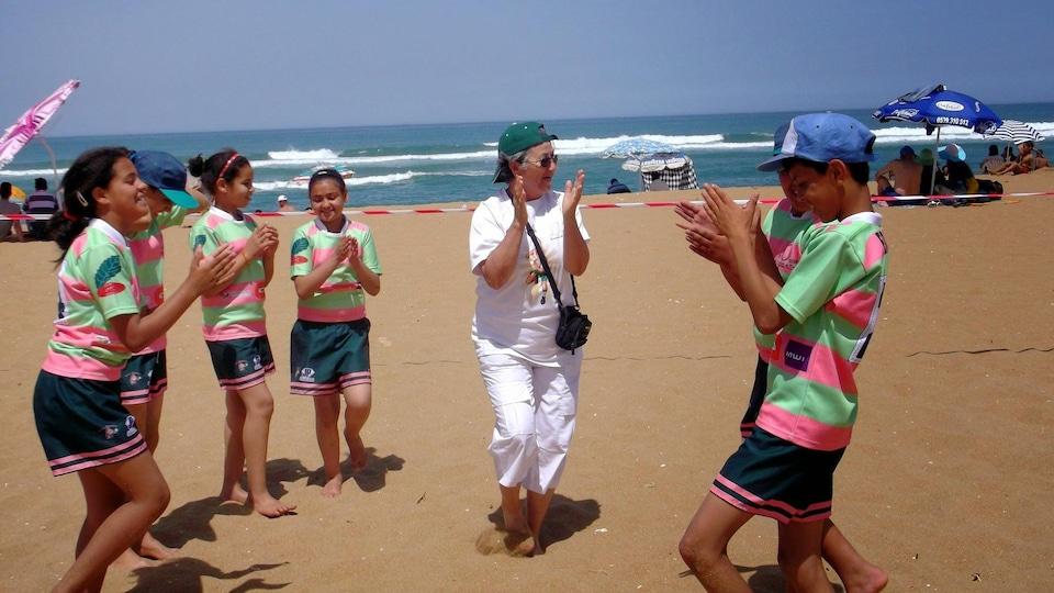 Saadia Ait Sghair sur une plage avec des enfants au Maroc.