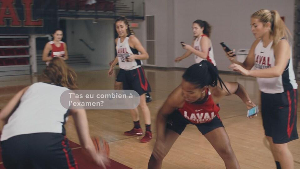 Des athlètes du Rouge et Or jouent au basketball en textant