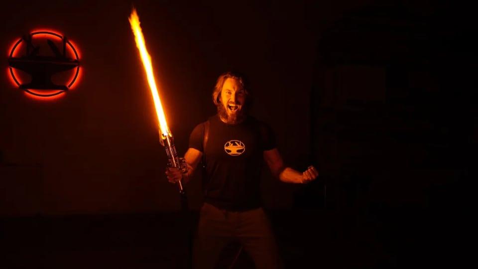 Un homme tient un sabre laser orange dans une pièce sombre.