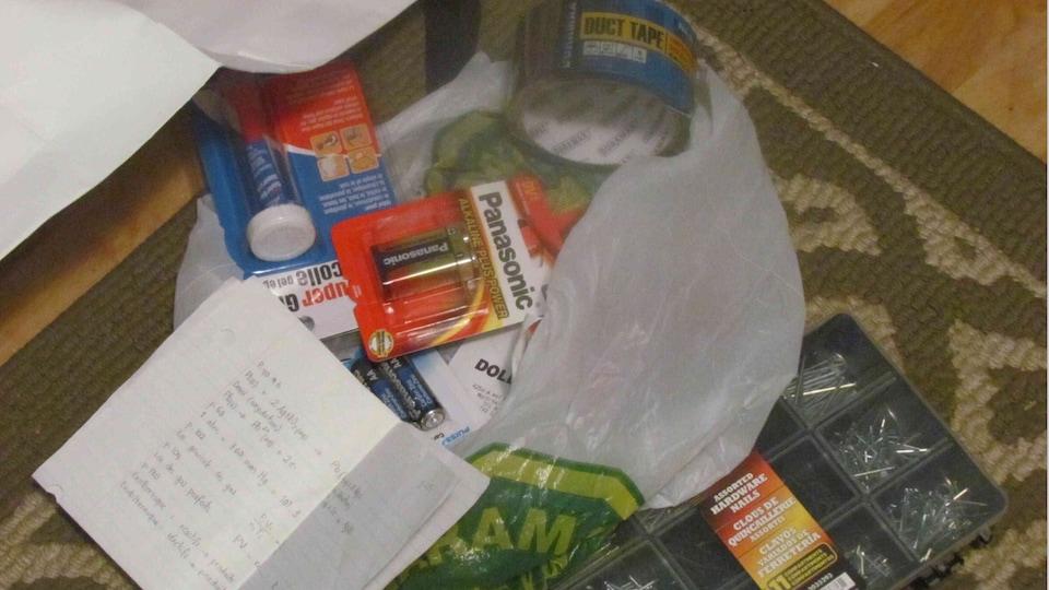 Un sac de plastique du magasin Dollarama qui contient notamment des clous, de la colle, des piles et du ruban adhésif.