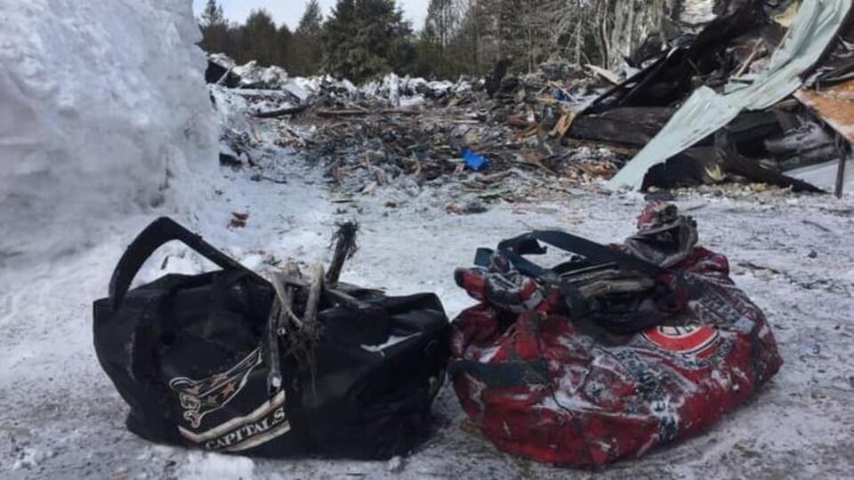 Deux sacs de hockey noircis par les flammes devant les débris de la résidence incendiée.