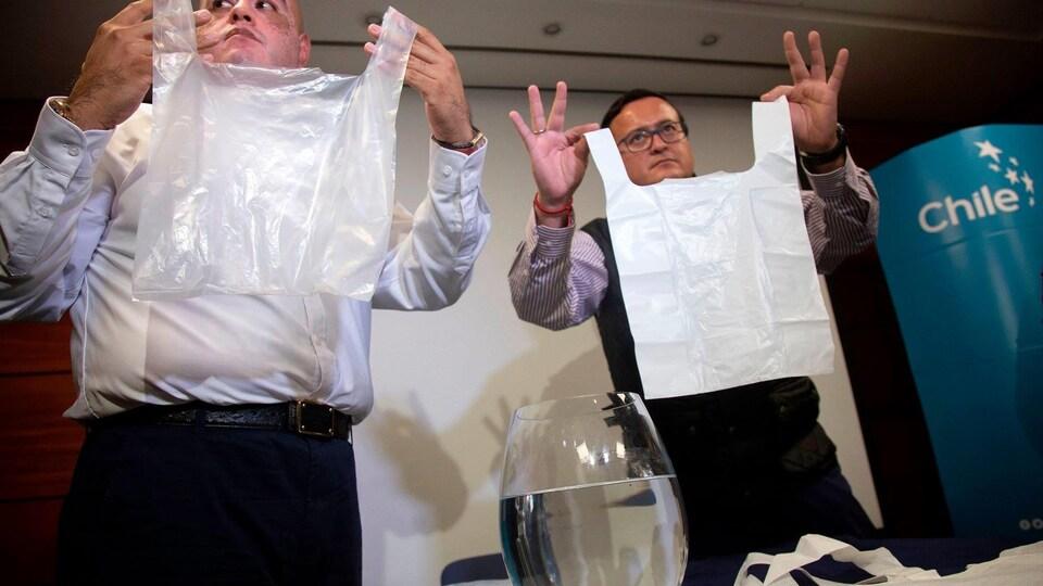 Deux chercheurs brandissent leurs sacs fabriqués à base de calcaire devant un verre d'eau.