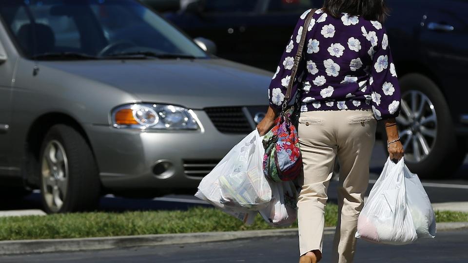 Une dame marche en tenant quatre sacs de plastique.