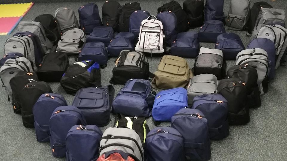 Des sacs à dos sur le sol.