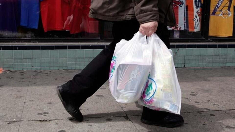 Un passant portant son épicerie dans des sacs jetables.