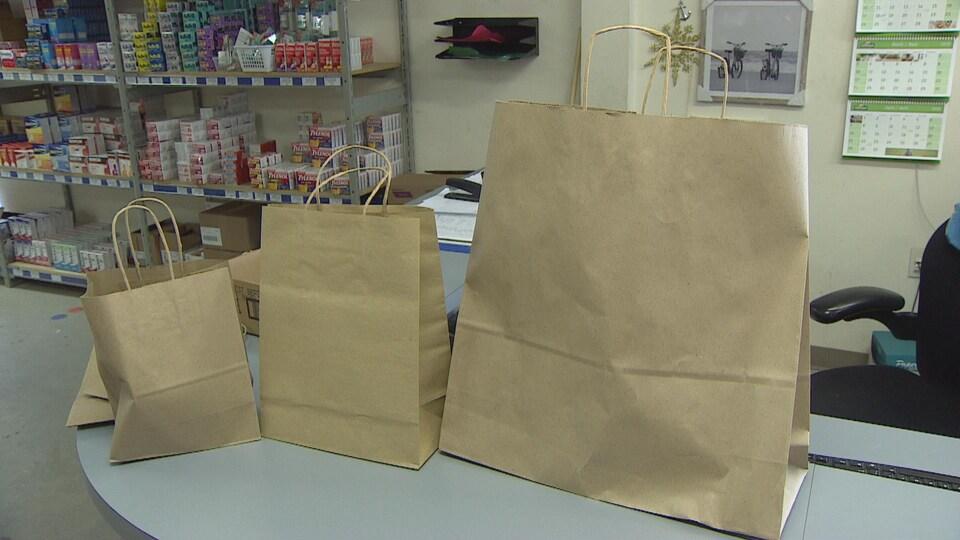 Trois sacs en papier sont exposés du plus petit au plus grand sur un comptoir.