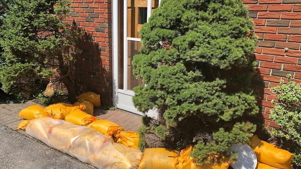 Des sacs de sable sont entassés devant une maison