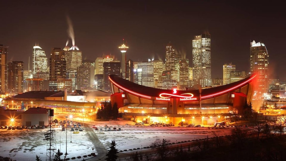 Une photo prise de nuit du Saddledome. En arrière-plan, des gratte-ciel sont illuminés.