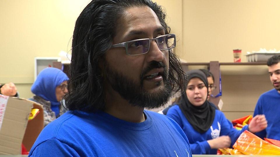 Sadique Pathan, relationniste pour la branche d'Edmonton de l'organisation Islamic Relief Canada, porte un gilet bleu, à l'instar des autres bénévoles participant à la distribution.