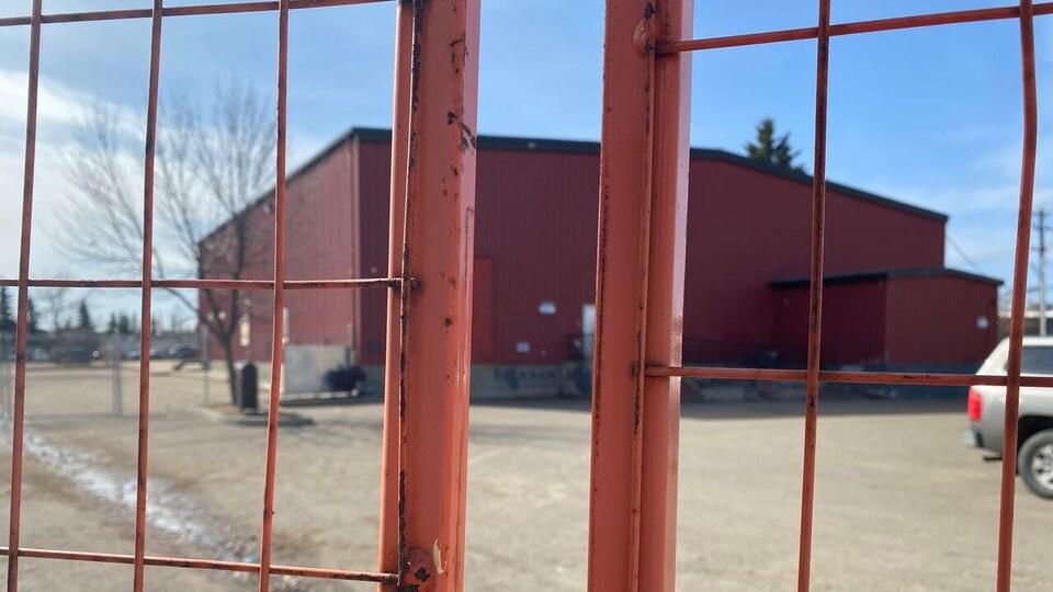 Un bâtiment carré rouge vu à travers une clôture.