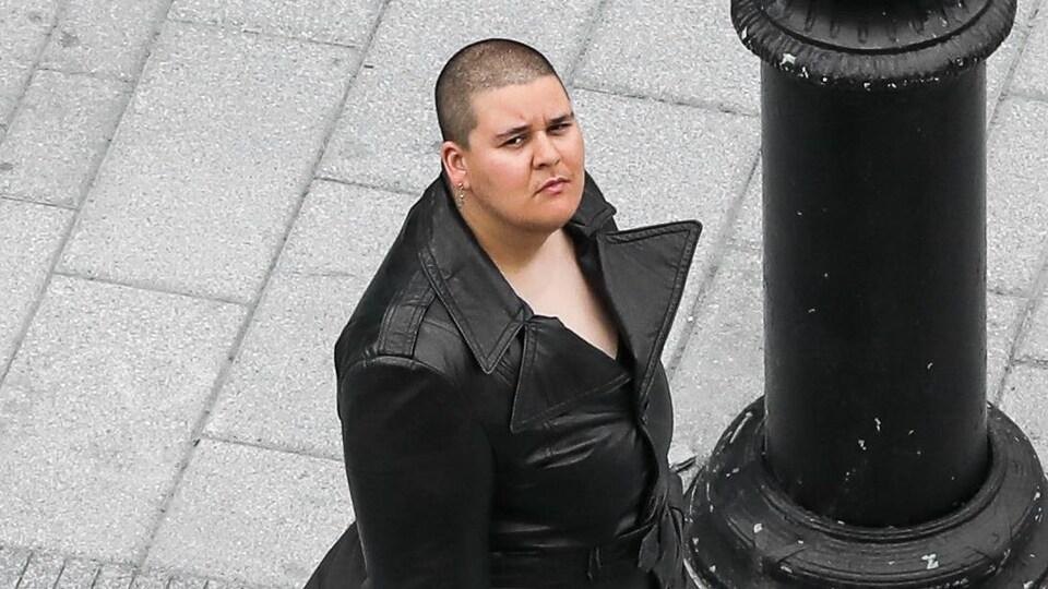 Une femme dans un long manteau de cuir regarde vers le haut sur un trottoir.