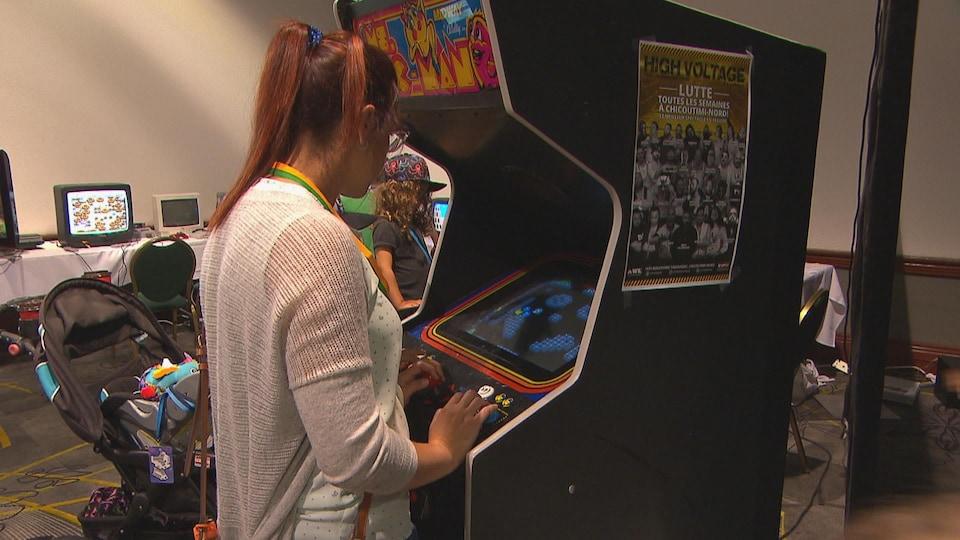 Une femme joue à un jeu vidéo.
