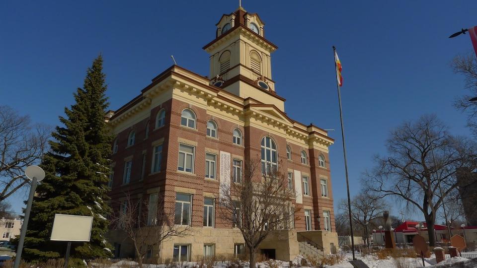 Un édifice en brique de quatre étages avec une tour munie d'une horloge.