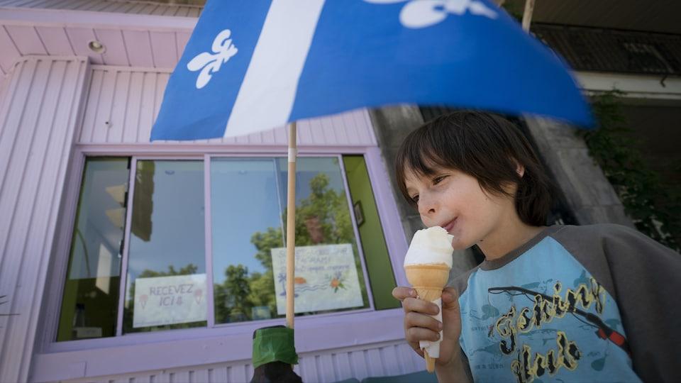 Un garçon mange une crème glacée près d'un drapeau du Québec.