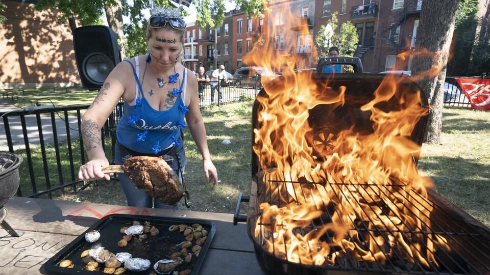 Une femme tient une grosse pièce de viande près d'un barbecue rempli de flammes.