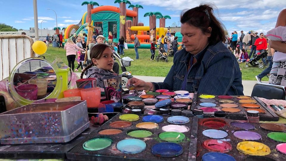 Une dame s'apprête à maquiller une enfant. Étalage des pots de couleur en avant-plan et des jeux gonflables à l'arrière