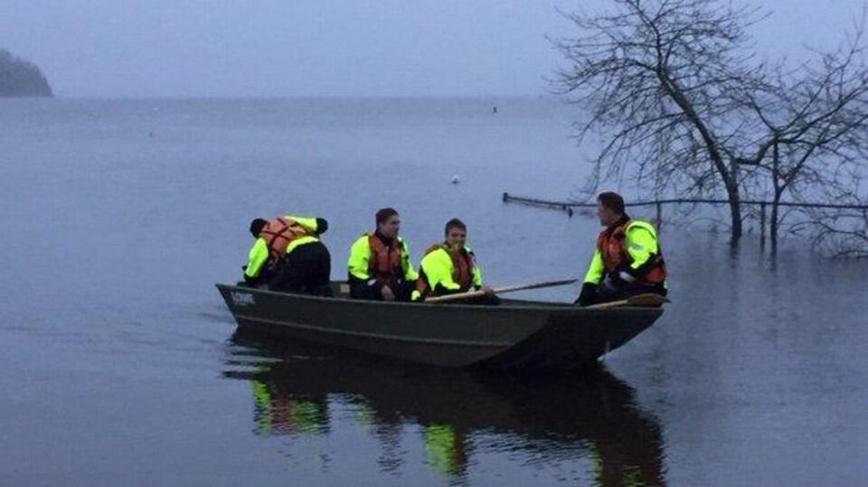 Quatre pompiers sur un petit bateau près de la rive
