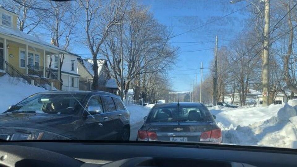 Un véhicule parvient à circuler dans un étroit passage entre la neige et une voiture garée le long de la rue.