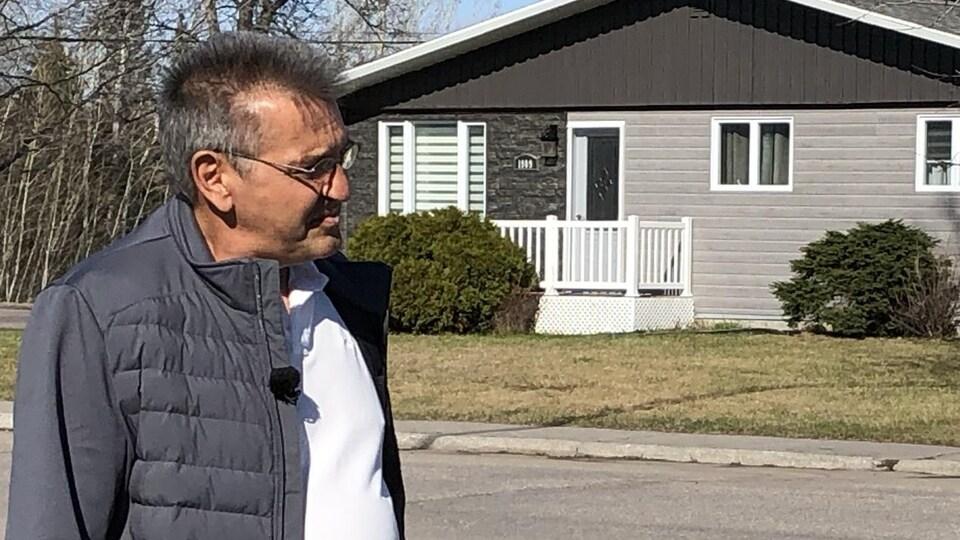 Un homme devant une maison.